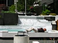 Człowiek odpoczywa obok fontanny przed budynkiem