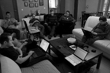 Na sofach siedzą: Tomasz Dominikowski, Sara Prussak, Stefan Plewako, Krzysztof Kurzawski, Piotr Drąg, Marek Stępień i Adriank Kalla, większość z laptopami.
